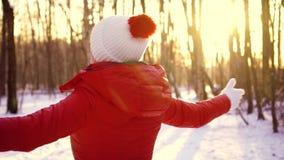 Mujer que disfruta de día de invierno al aire libre Muchacha feliz que aumenta los brazos para arriba en la cámara lenta y que gi almacen de video