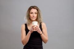 Mujer que disfruta de la bebida caliente en taza de papel disponible Fotos de archivo