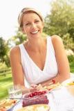 Mujer que disfruta de la comida en jardín fotografía de archivo libre de regalías