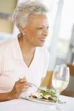 Mujer que disfruta de la comida, Mealtime con un vidrio de vino Fotos de archivo libres de regalías