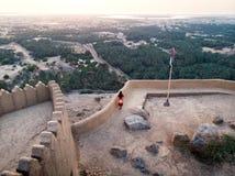 Mujer que disfruta de la opinión de la puesta del sol del fuerte de Dhayah en los UAE imagenes de archivo