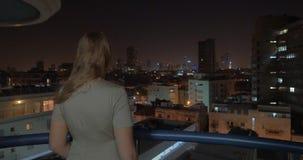 Mujer que disfruta de la vista de la ciudad de la noche del tejado Tel Aviv, Israel metrajes