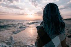 Mujer que disfruta de la vista de la puesta del sol en costa de mar imagenes de archivo