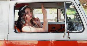 Mujer que disfruta de música mientras que se sienta en la autocaravana 4k metrajes
