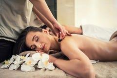 Mujer que disfruta de masaje de piedra caliente tradicional al lado de su socio Imagen de archivo