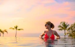 Mujer que disfruta de puesta del sol mientras que se relaja en piscina del infinito Foto de archivo
