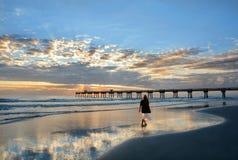 Mujer que disfruta de tiempo en la playa hermosa en la salida del sol Imagenes de archivo