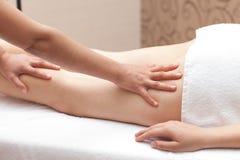 Mujer que disfruta de un masaje de la pierna en una configuración del balneario Foto de archivo