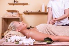 Mujer que disfruta de un masaje en un balneario Foto de archivo