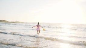 Mujer que disfruta de un paseo a lo largo de la playa metrajes