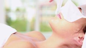 Mujer que disfruta de un tratamiento facial almacen de video
