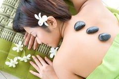 Mujer que disfruta de una terapia de piedra de relajación Fotografía de archivo libre de regalías