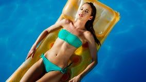 Mujer que disfruta de verano en el colchón fotos de archivo