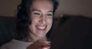 Mujer que disfruta del contenido de los medios en la tableta digital almacen de metraje de vídeo