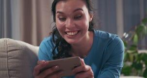 Mujer que disfruta del contenido en línea de los medios en el teléfono en casa almacen de metraje de vídeo