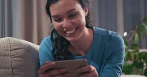 Mujer que disfruta del contenido en línea de los medios en el teléfono móvil almacen de video