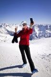 Mujer que disfruta del esquí en las montañas Imagen de archivo