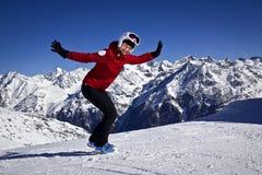 Mujer que disfruta del esquí en las montañas Foto de archivo libre de regalías