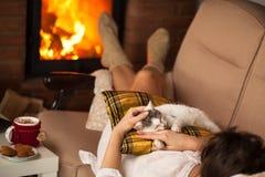 Mujer que disfruta del fuego y de una cierta compañía fina - su gatito Foto de archivo libre de regalías