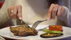 Mujer que disfruta del gusto del filete asado a la parrilla en restaurante almacen de metraje de vídeo