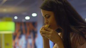 Mujer que disfruta del gusto y del aroma de la hamburguesa, sentándose en el restaurante de los alimentos de preparación rápida metrajes