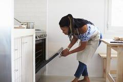 Mujer que dobla abajo para mirar en el horno en su cocina Imágenes de archivo libres de regalías