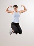 Mujer que dobla el bíceps mientras que salta en mid-air imagenes de archivo