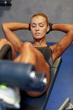Mujer que dobla los músculos abdominales en banco en gimnasio Imagenes de archivo