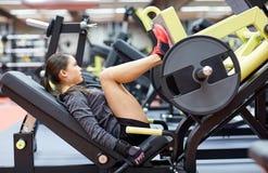 Mujer que dobla los músculos en la máquina de la prensa de la pierna en gimnasio foto de archivo libre de regalías