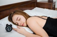 Mujer que duerme con el despertador Fotografía de archivo