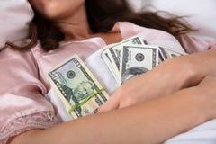 Mujer que duerme con el paquete de notas de la moneda fotos de archivo libres de regalías