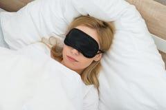 Mujer que duerme con la máscara del sueño Foto de archivo