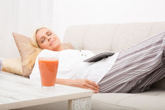 Mujer que duerme con la tableta en el sofá Imagenes de archivo