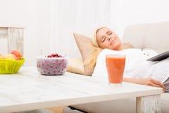 Mujer que duerme con la tableta en el sofá Imágenes de archivo libres de regalías