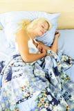 Mujer que duerme en cama Foto de archivo libre de regalías