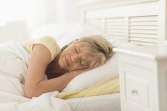 Mujer que duerme en cama Fotos de archivo