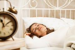 Mujer que duerme en cama al lado del despertador Imagenes de archivo