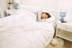 Mujer que duerme en cama al lado del perro feliz imágenes de archivo libres de regalías