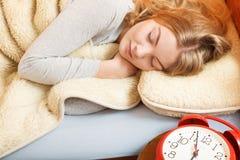 Mujer que duerme en cama con el despertador del sistema Imagen de archivo