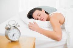 Mujer que duerme en cama con el despertador en la mesita de noche Foto de archivo libre de regalías