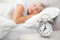 Mujer que duerme en cama con el despertador en primero plano en el dormitorio Imagen de archivo