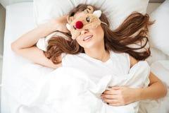 Mujer que duerme en cama con la máscara de ojo Foto de archivo libre de regalías