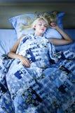 Mujer que duerme en cama en la noche Imágenes de archivo libres de regalías