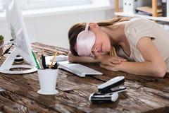 Mujer que duerme en el escritorio de oficina imagenes de archivo
