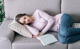 Mujer que duerme en el sofá Foto de archivo libre de regalías
