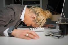 Mujer que duerme en el teclado de ordenadores en la oficina foto de archivo
