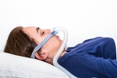 Mujer que duerme en ella detrás con CPAP, tratamiento del apnea de sueño Fotos de archivo libres de regalías
