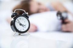 Mujer que duerme en la cama con la alarma Fotos de archivo
