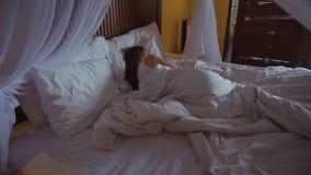 Mujer que duerme en la cama con los bedsheets blancos y el baldaquín en casa de planta baja romántica en Bali Indonesia almacen de video