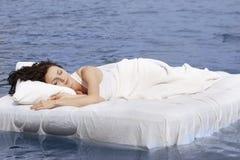 Mujer que duerme en la cama en el mar Imagenes de archivo